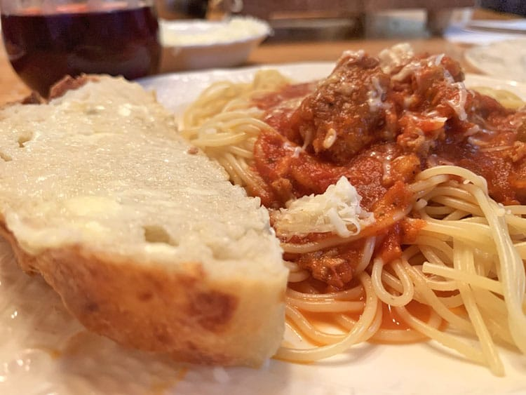 Slice of homemade bread with butter on it with a plate of spaghetti and sauce.