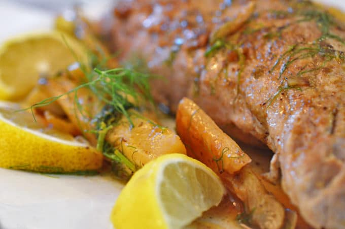Pork tenderloin with garnishes of fennel and garlic and a lemon wedge.