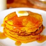 A stack of pancakes drizzled in syrup