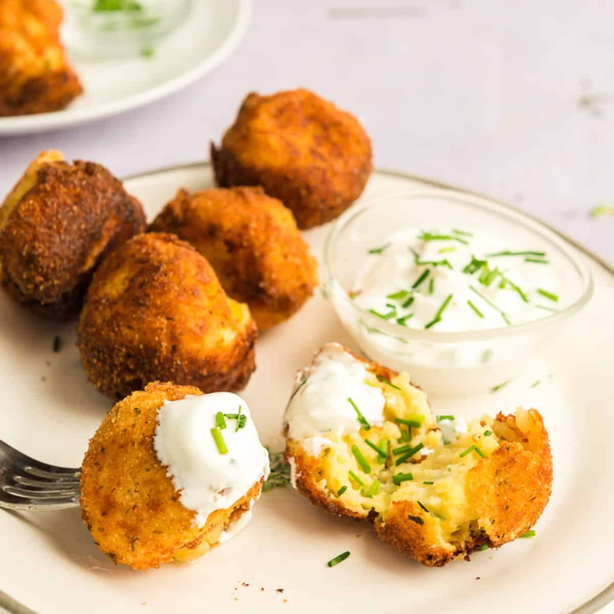 Plate of mashed potato croquettes with sour cream and chves.