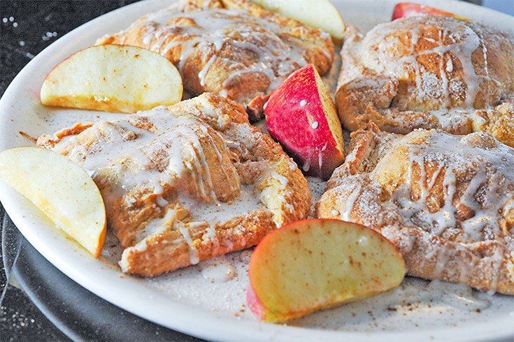 Plate of apple turnovers with slices of apple.