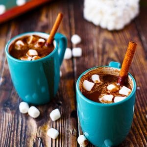 Two blue mugs of vegan hot chocolate with marshmallows and cinnamon sticks.