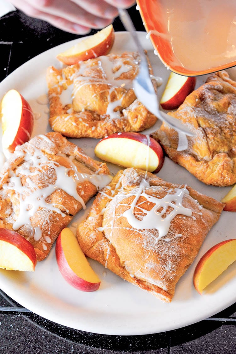 Drizzling glaze over apple turnovers