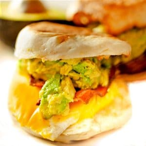English muffin breakfast sandwich with avocado and cheddar cheese oozing out.