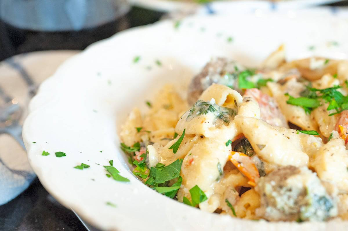 Serving plate of creamy pasta and sausage, garnished with parsley.
