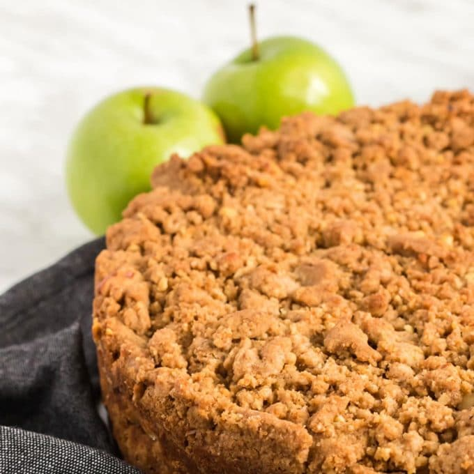 A cake topped with a crumb topping and two Ganny Smith apples
