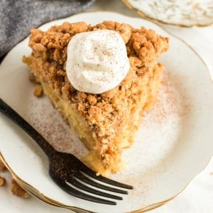 A slice of apple dessert on a plate with sour cream topping