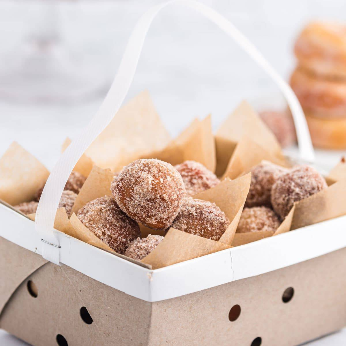 A box of donut holes coated with sugar.
