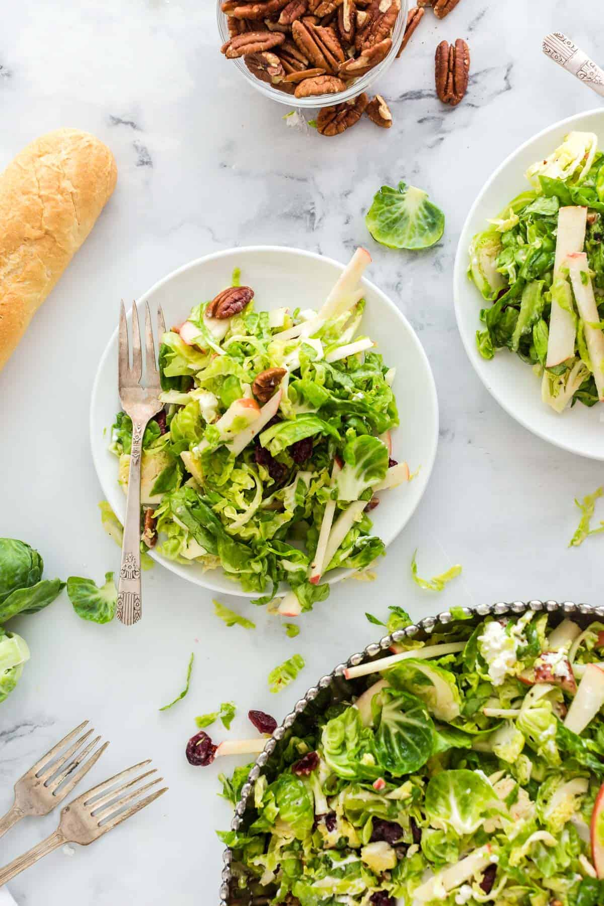 Three bowls of Brussels sprouts salad with walnuts and a baguette of bread