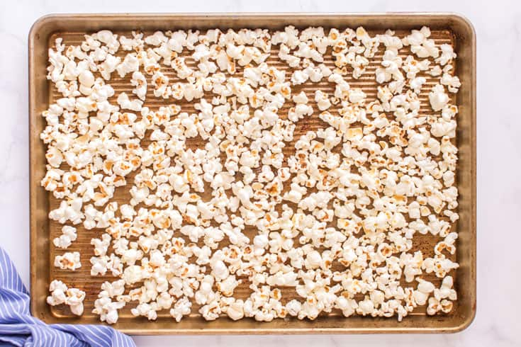 Single layer of popcorn on a rimmed baking sheet.