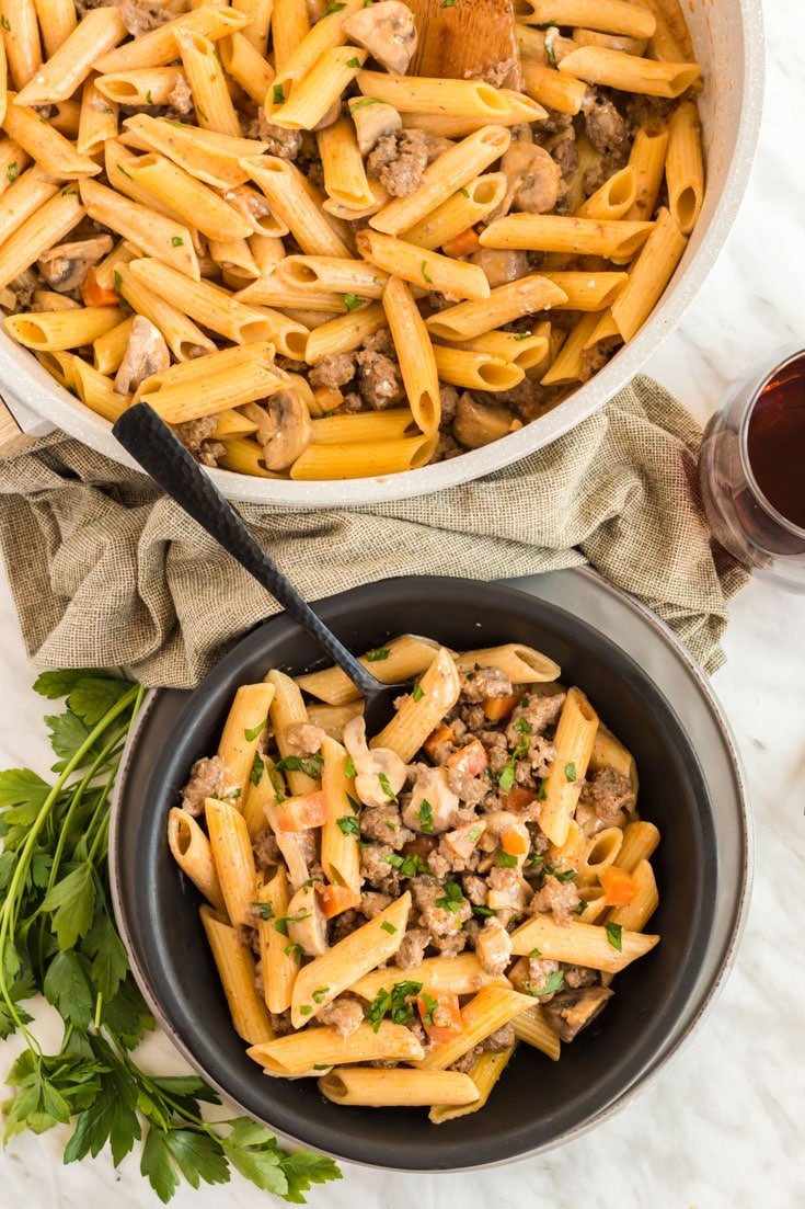 Skillet of beef and pasta and a filled serving bowl.