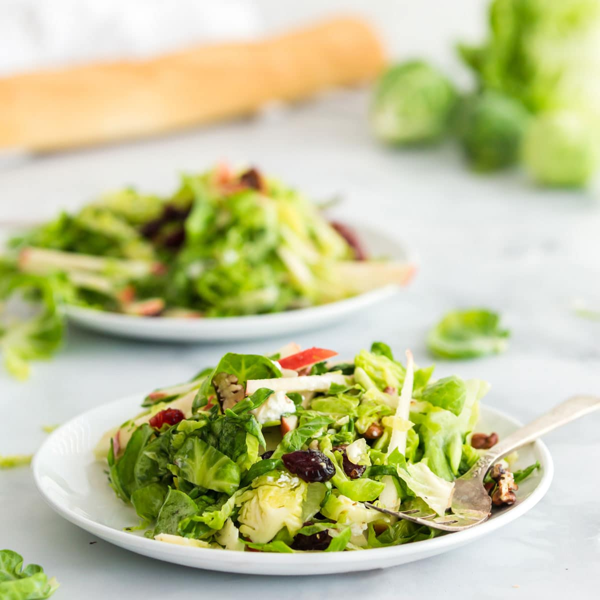 Two bowls of salad with Brussels sprouts