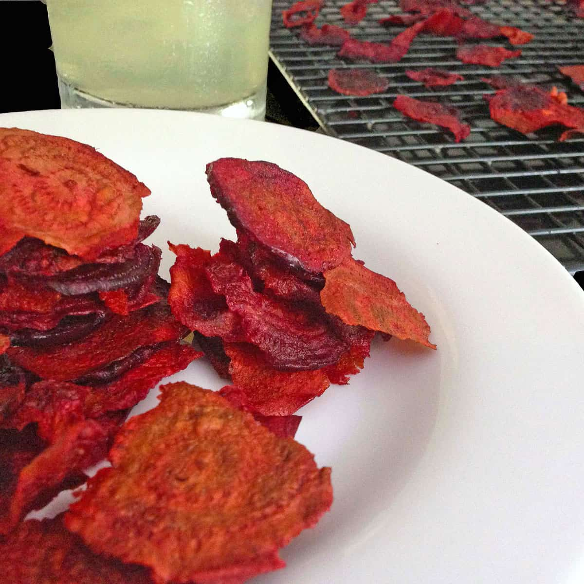 A plate of beet chips and a glass of lemonade.