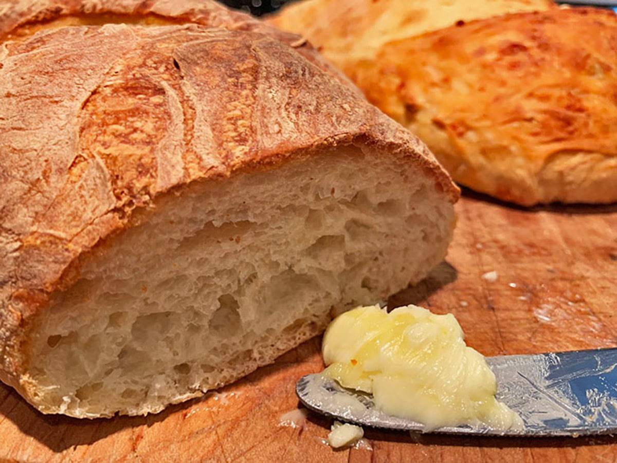 A loaf of bread cut in half with a knife and butter