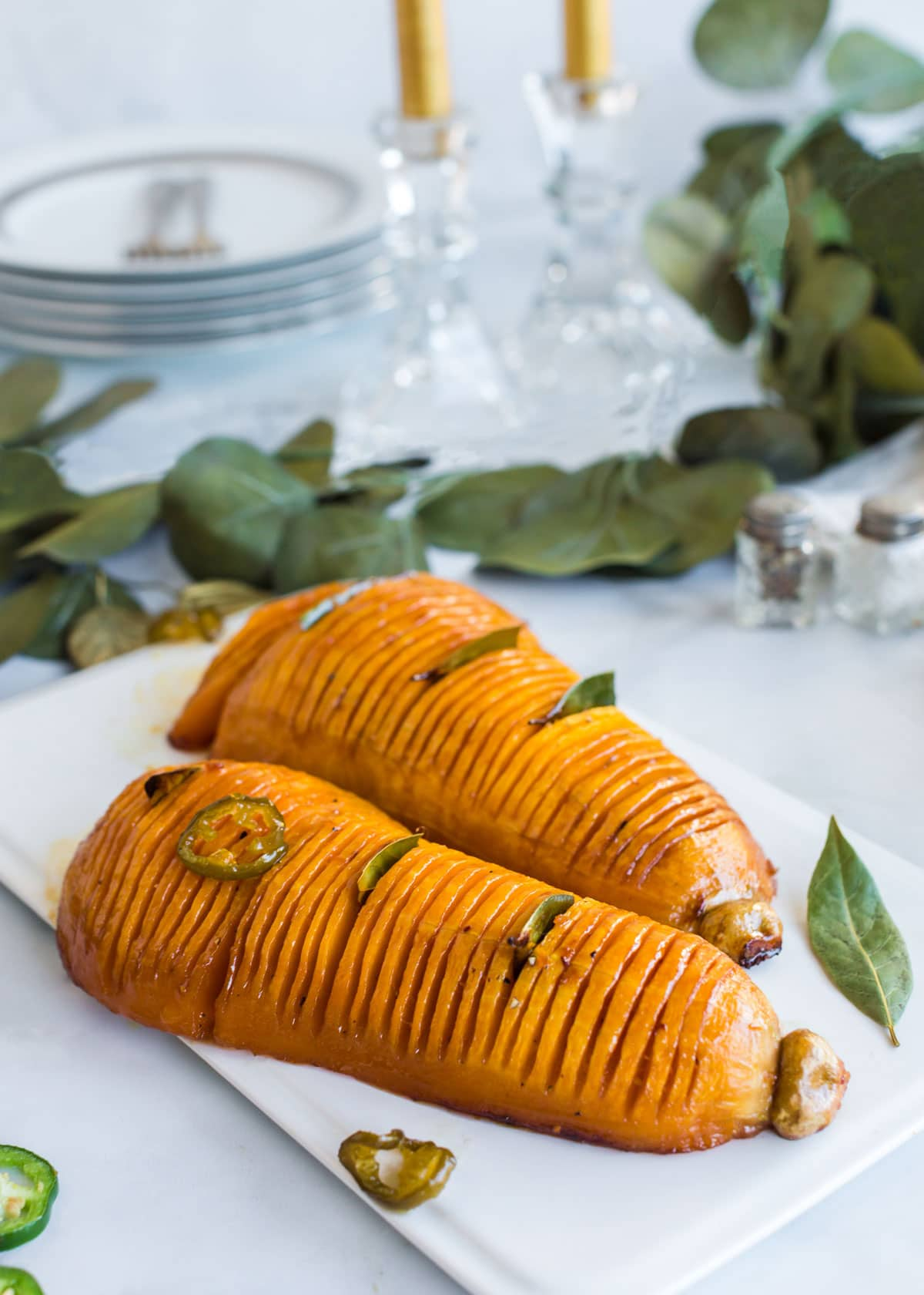 Two hasselback butternut squash on a serving plate