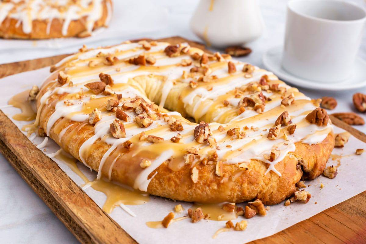 A Danish kringle on a cutting board with nuts and frosting.