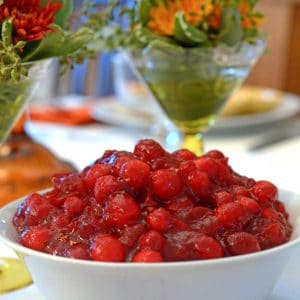 A bowl of cranberries with flower arrangement in background