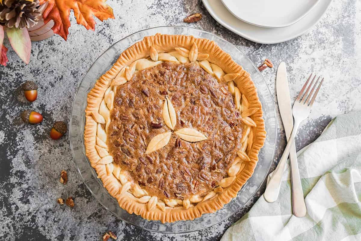 A homemade pie with acorns and fall leaves on the side.