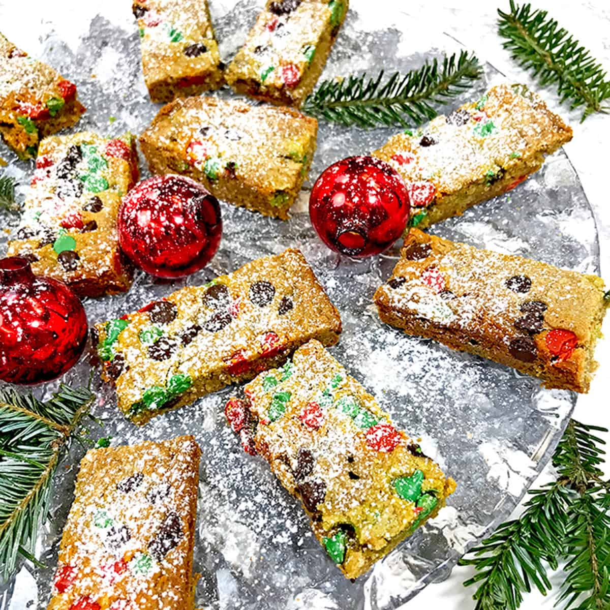 A festive plate of Christmas cookie bars with red ornaments.