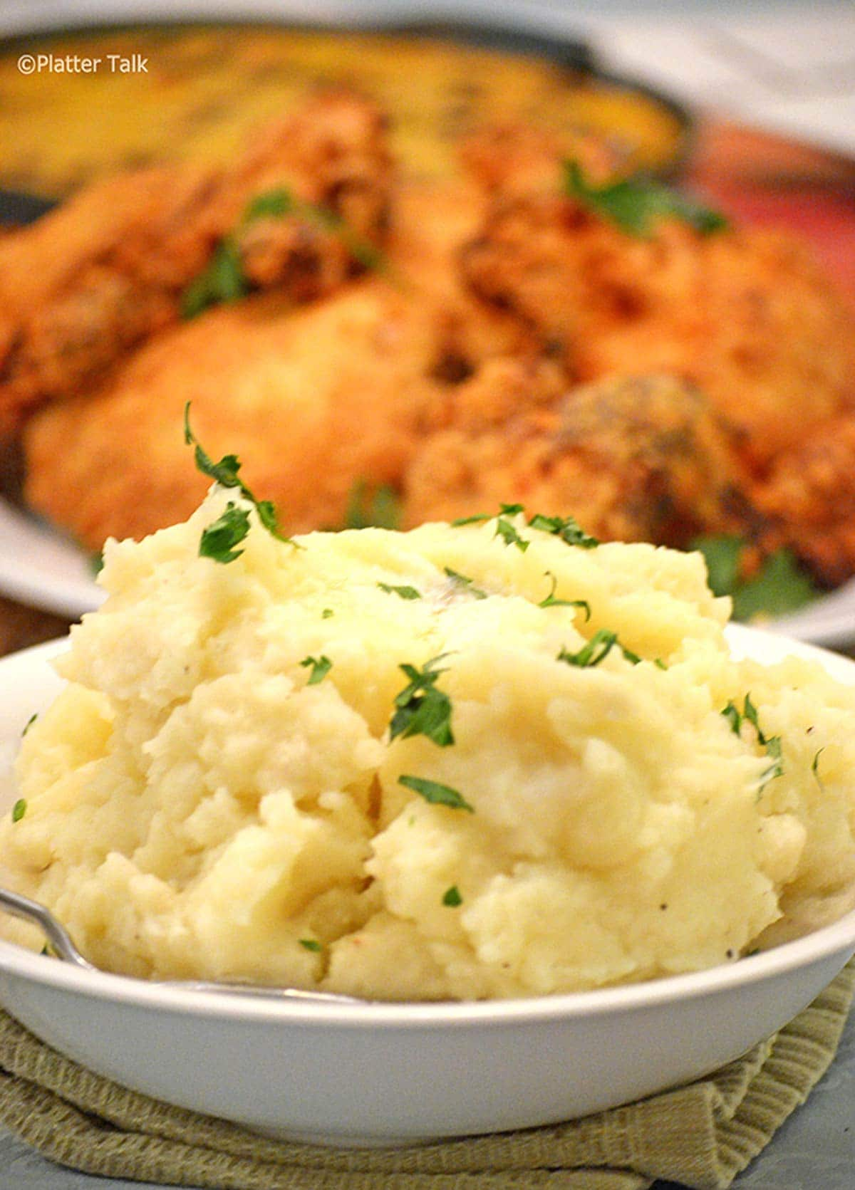 A bowl of mashed potatoes on a table with fried chicken in background.