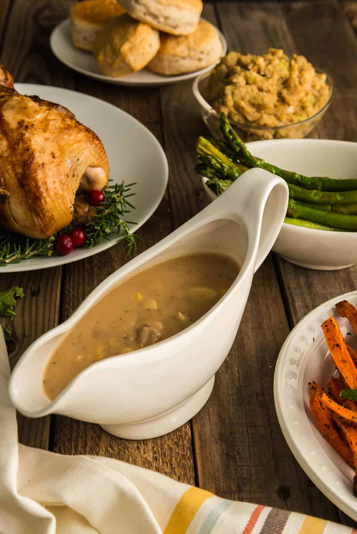A serving dish of giblet gravy and other holiday food on a table.