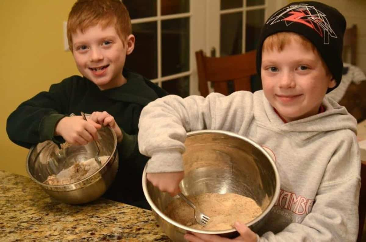 Two young boys mixing pie ingredients in mixing bowls.