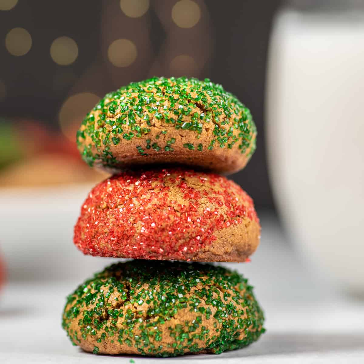 a stack of colored crinkle cookies with a glass of milk