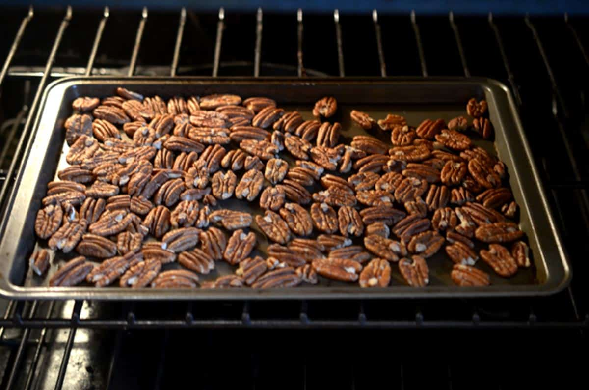 A sheet pan of pecans toasting in the oven.