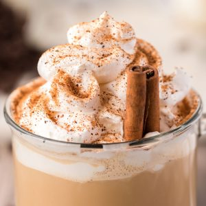 Closeup of a homemade latte topped with whipped cream and cinnamon