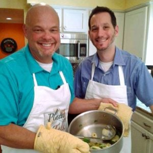 Two men standing in a kitchen with a pot of food.