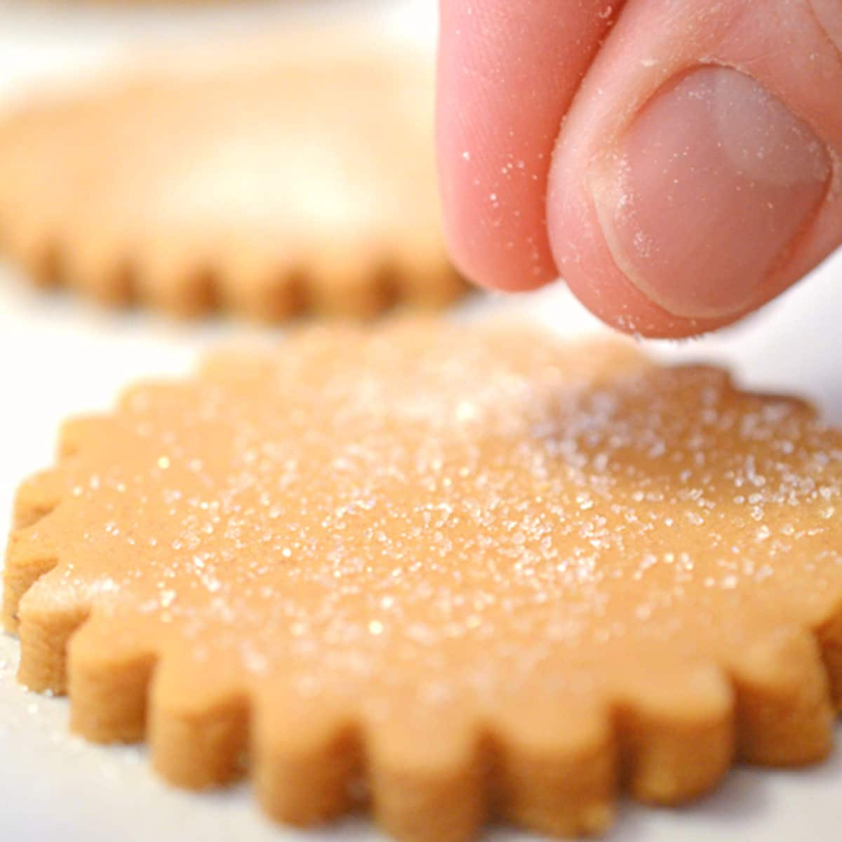 Sprinkling sugar on an unbaked cookie.