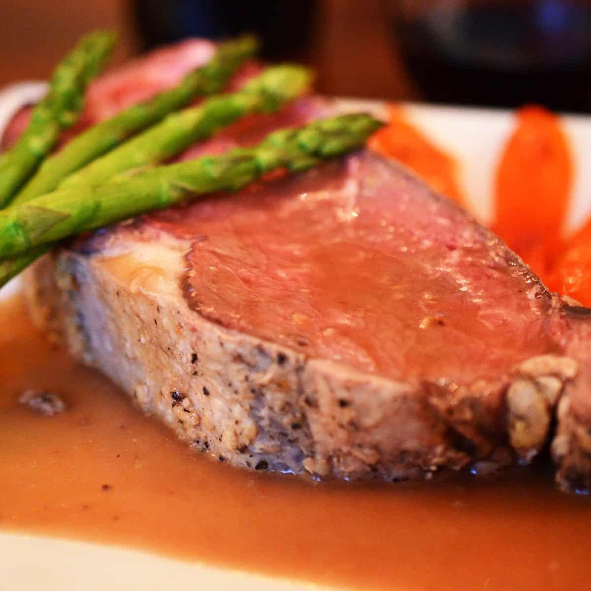 A plate of medium-rare prime rib with asparagus and carrots.