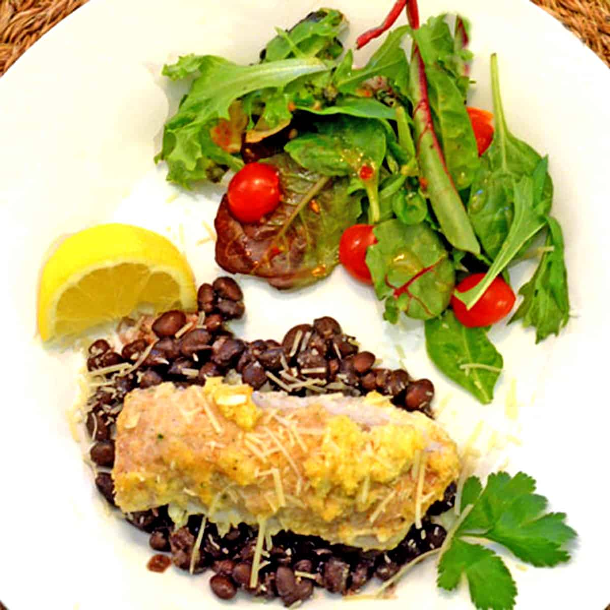 A dinner plate with fish over black beans and a salad.