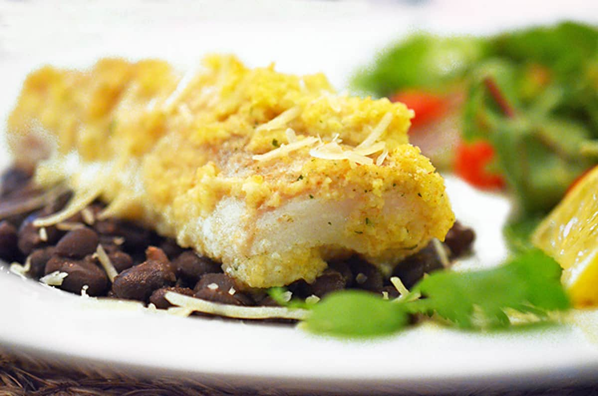 A plate of baked whitefish over black beans.
