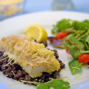 a plate of baked fish over black beans and green salad