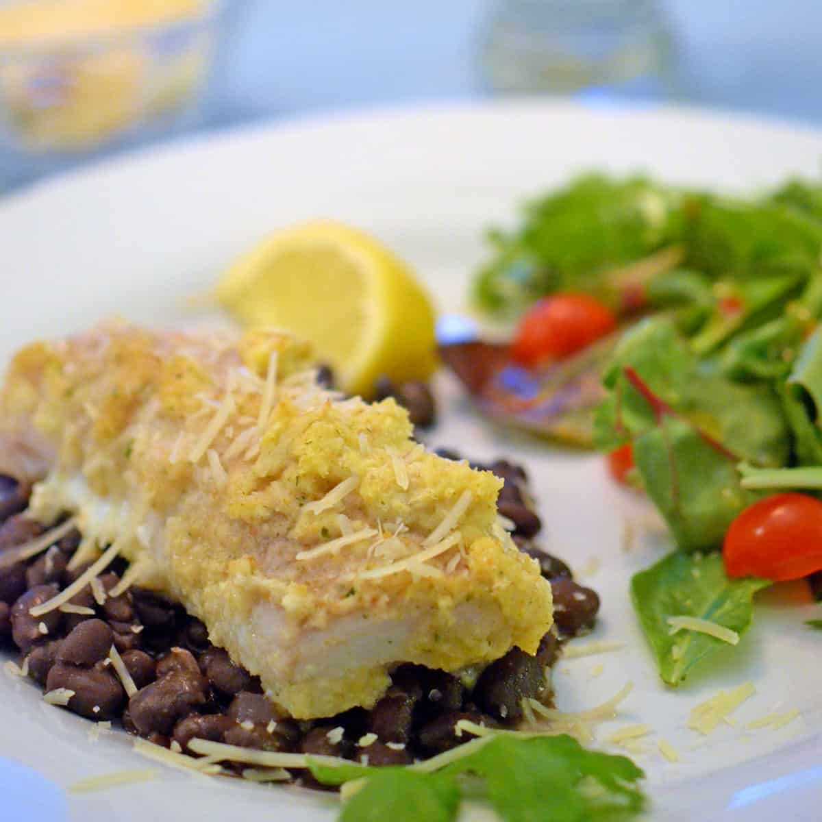 A plate of food with whitefish and black beans and green salad.