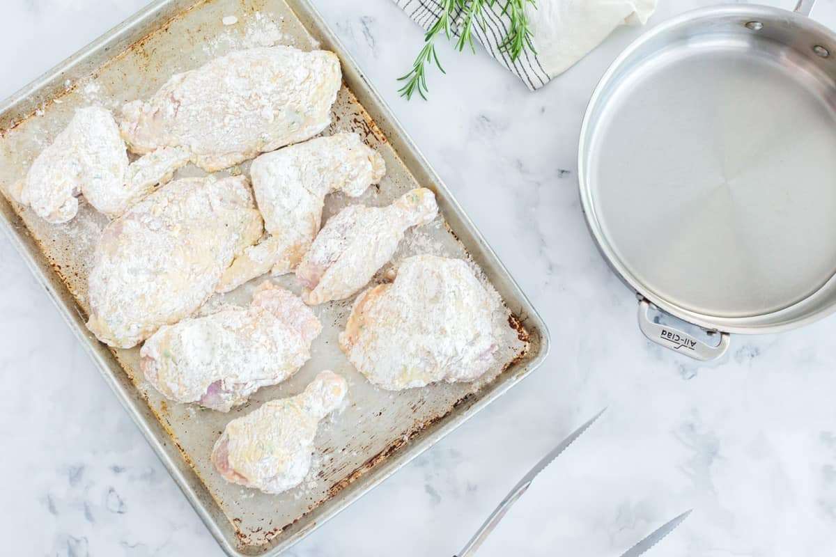 A bunch of chicken covered with flour and sitting on a baking pan.