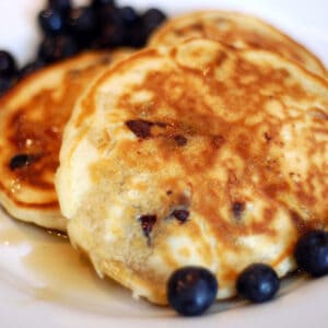 A closeup of pancakes with blueberries and syrup.