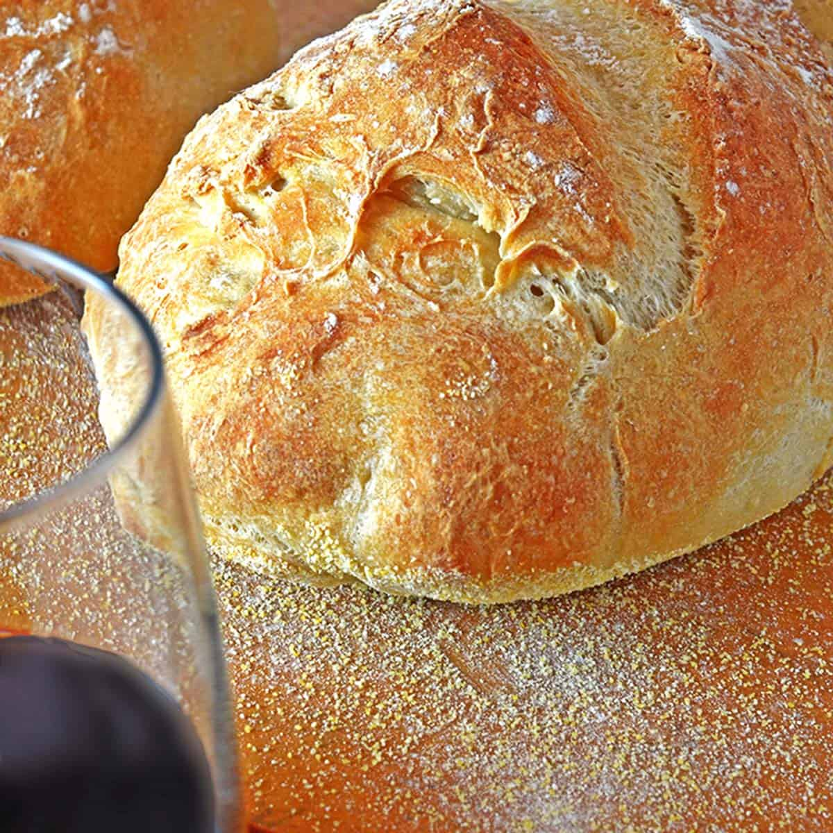 A loaf of bread with a glass of red wine.
