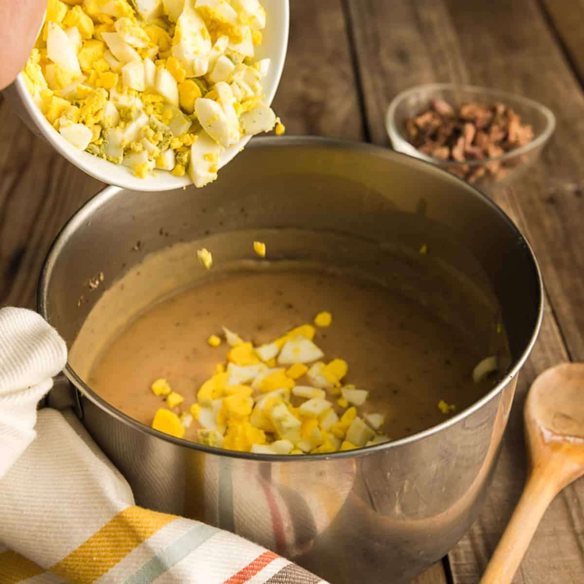 Adding chopped hard boiled eggs to a pot of gravy.
