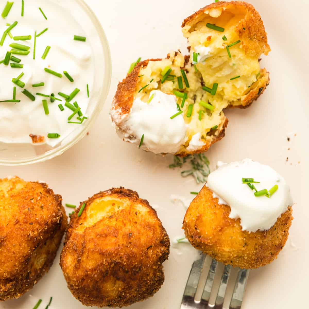 A plate of potato croquettes with sour cream.