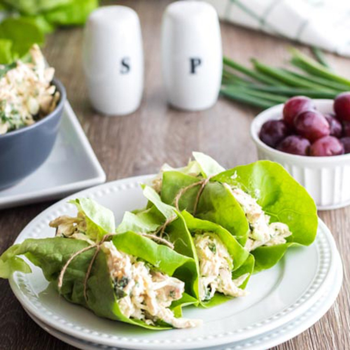 A plate of chicken salad wraps and a dish of grapes.