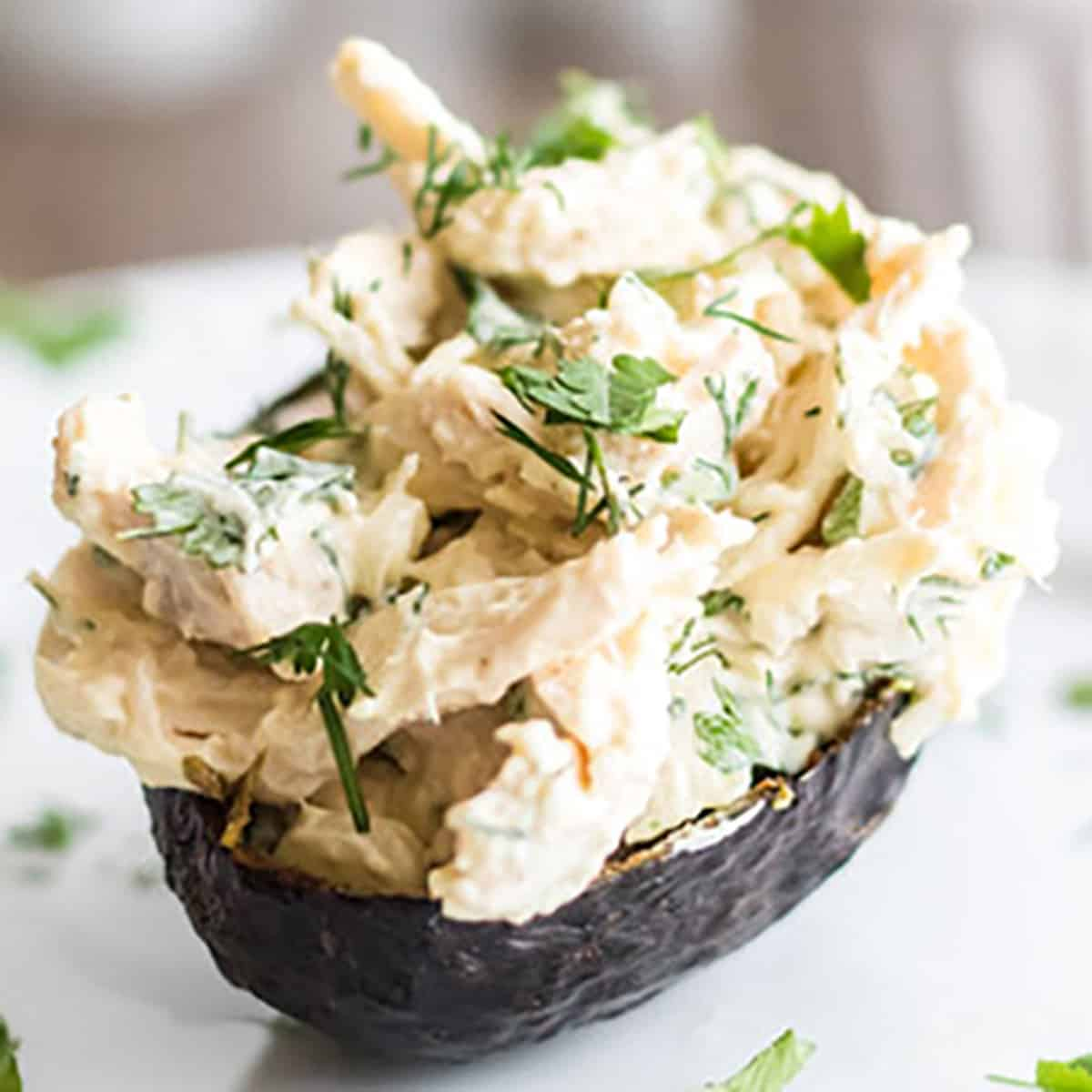 An avocado stuffed with chicken salad.