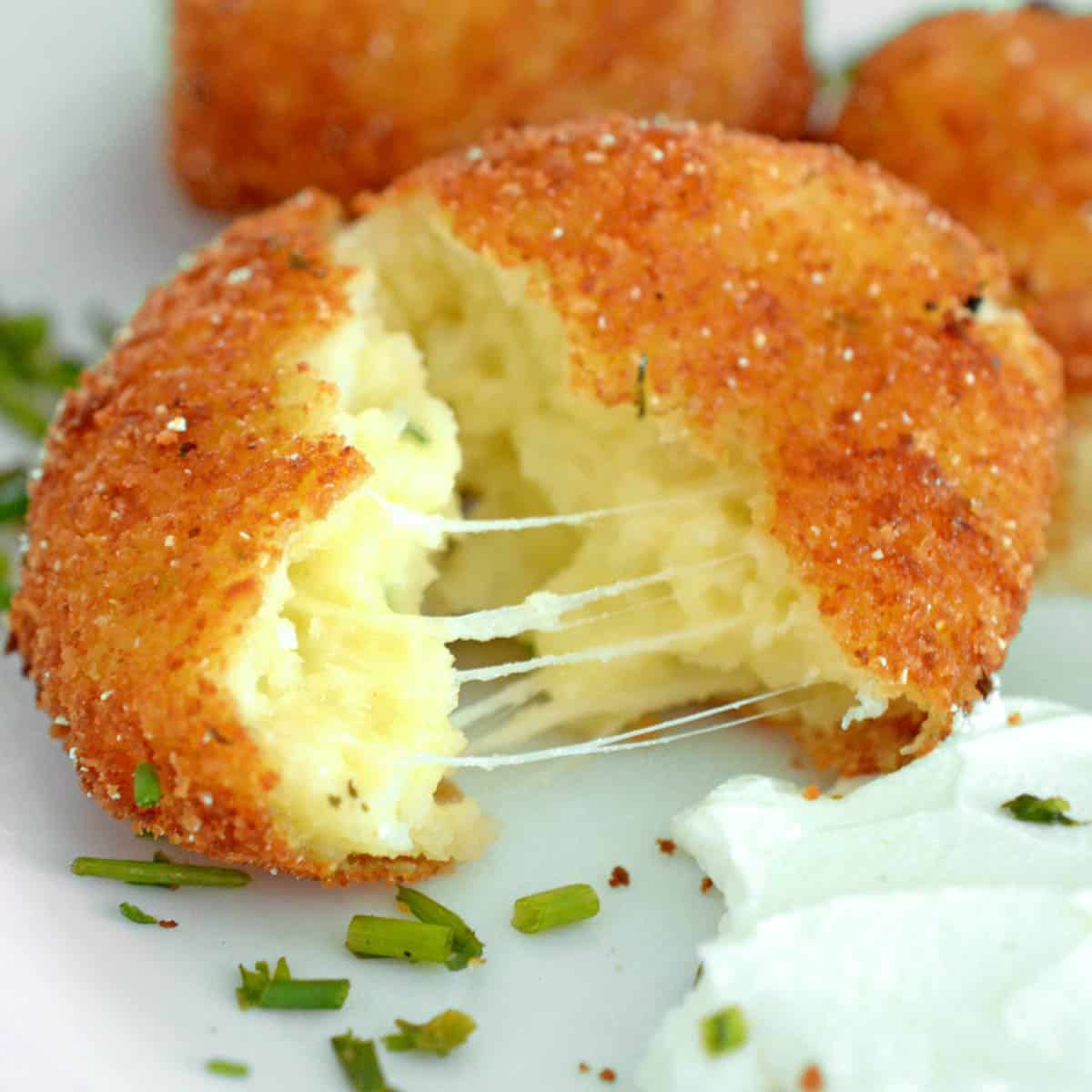 A croquette split open with stringy cheese.
