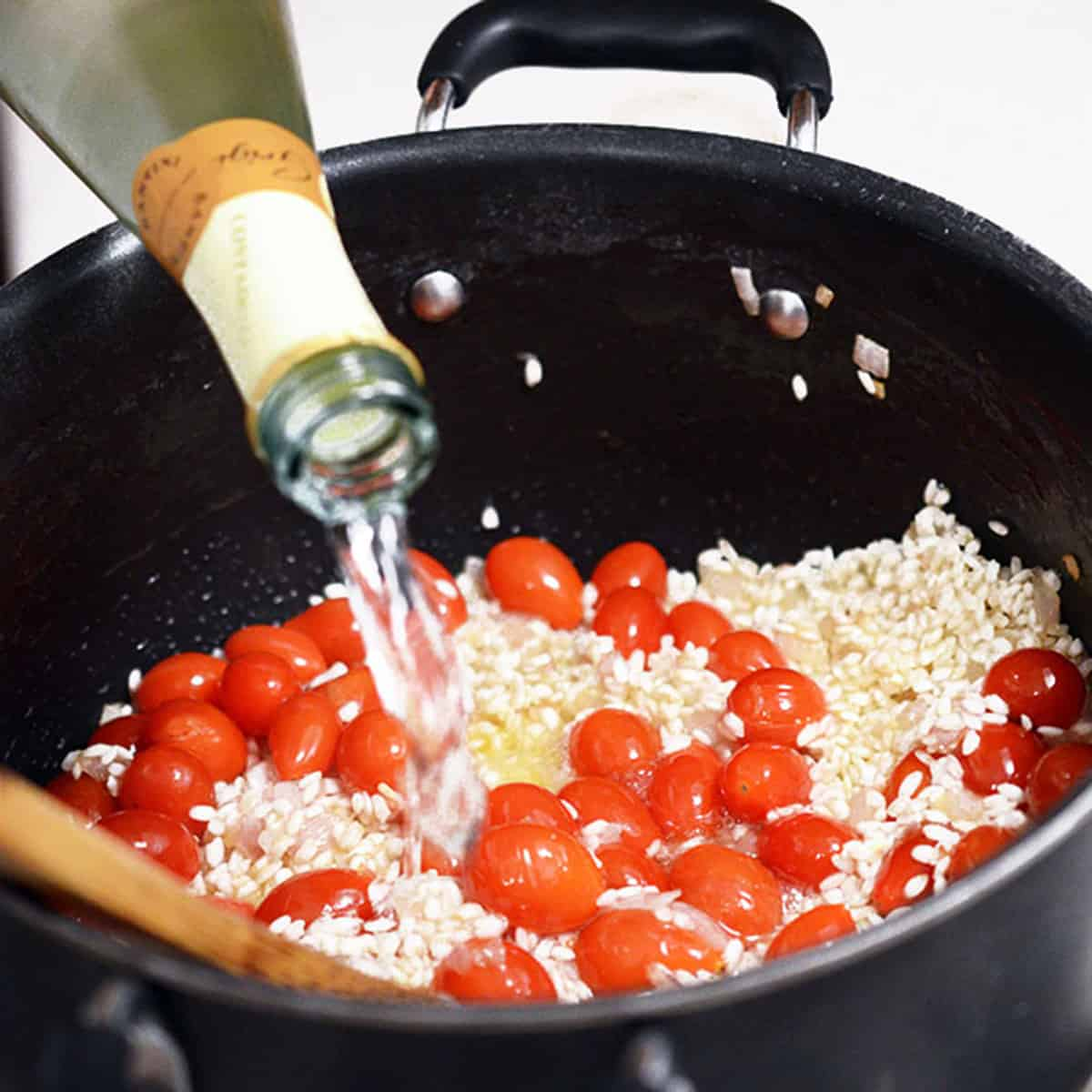 Adding white wine to risotto and tomatoes.