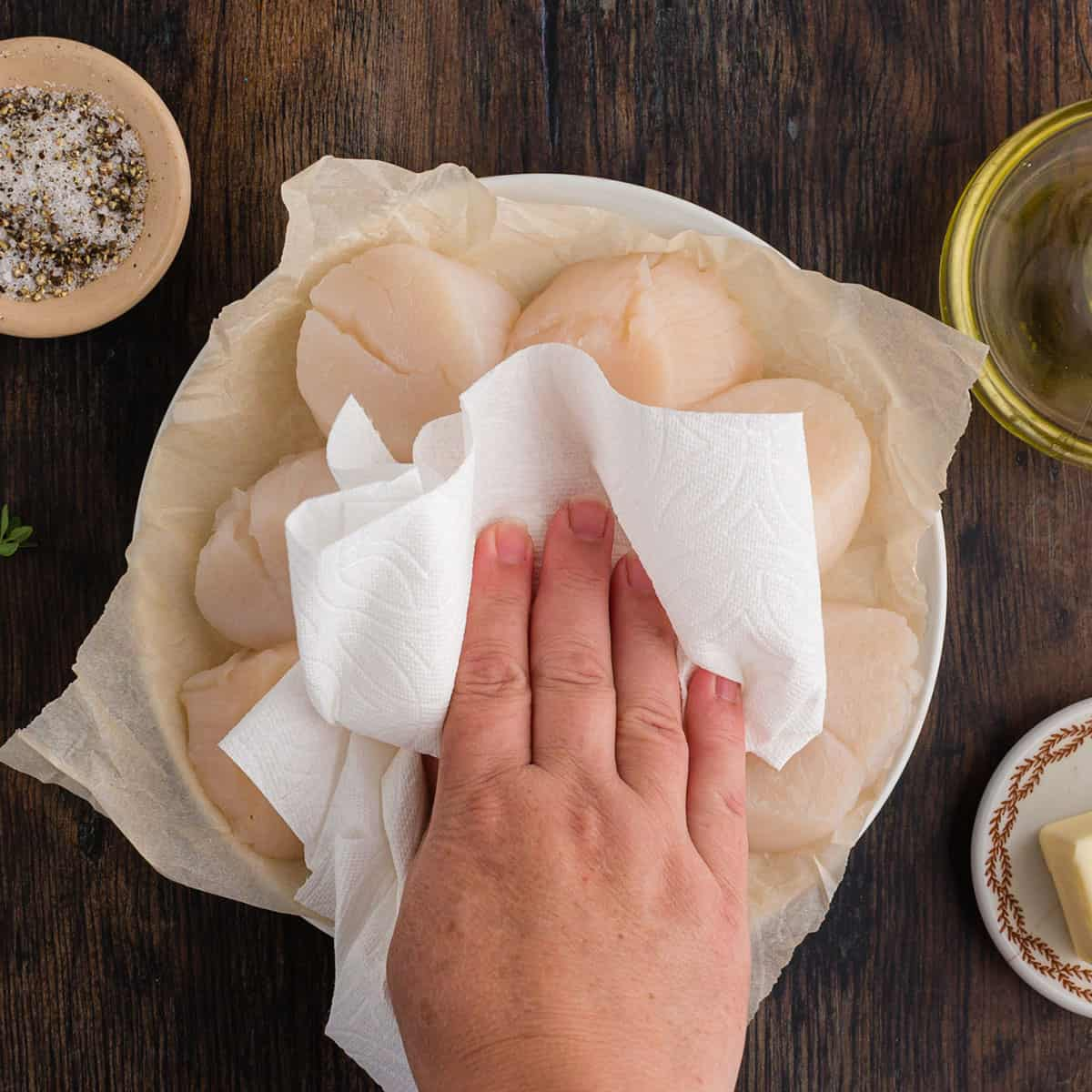 Blotting scallops dry with a paper towel.