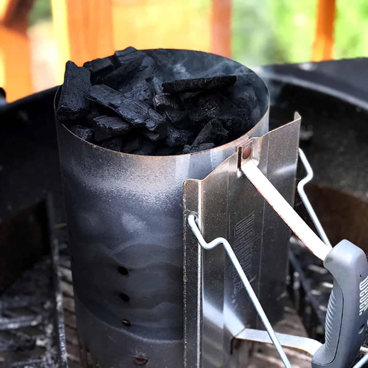 a charcoal chimney that has just been lit, sitting in a grill.