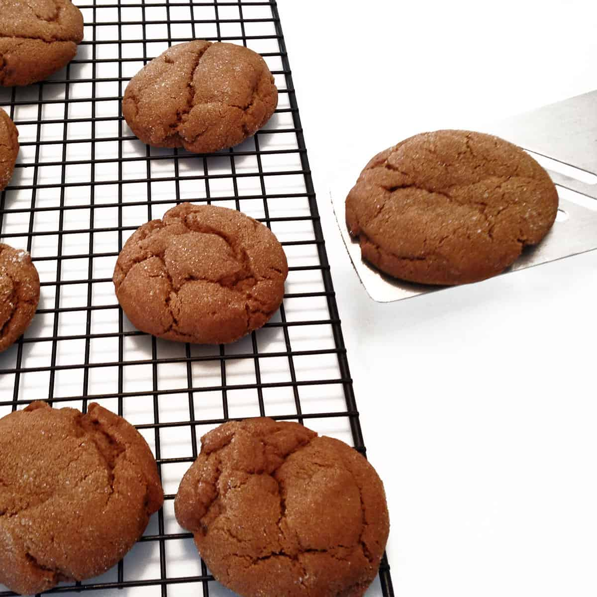 Molasses cookies being placed on a cooling rack, using a spatula.