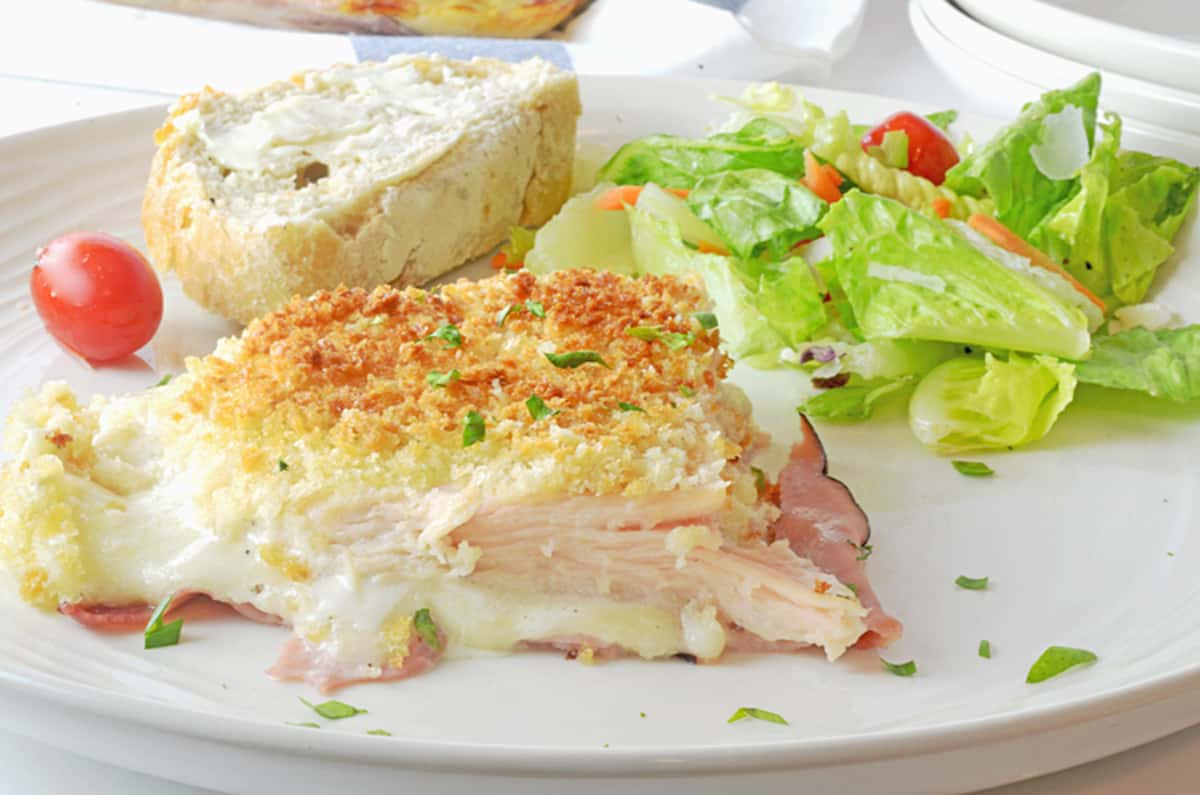 A serving of chicken cordon bleu casserole with salad and bread.