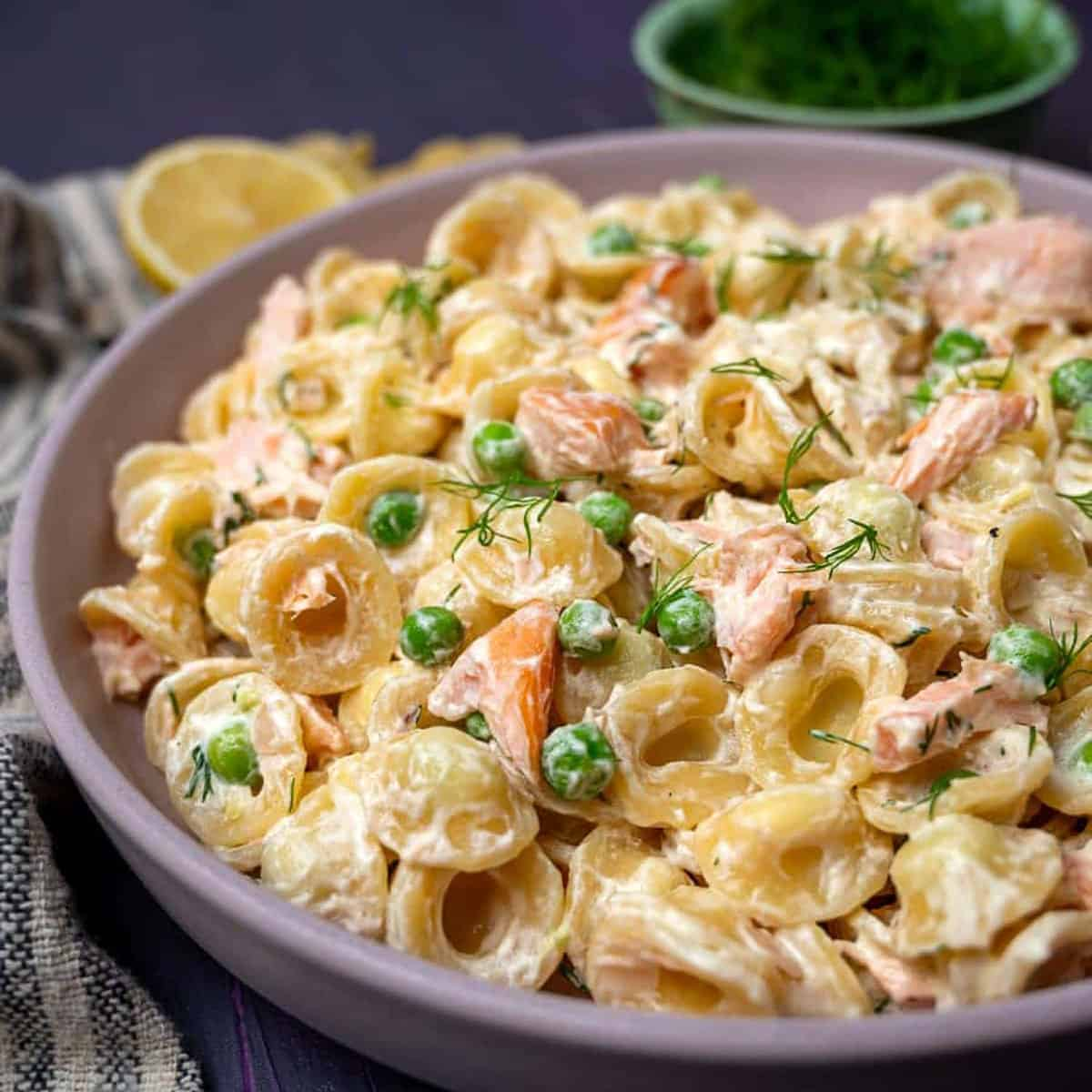 A bowl of creamy pasta with peas and smoked salmon.